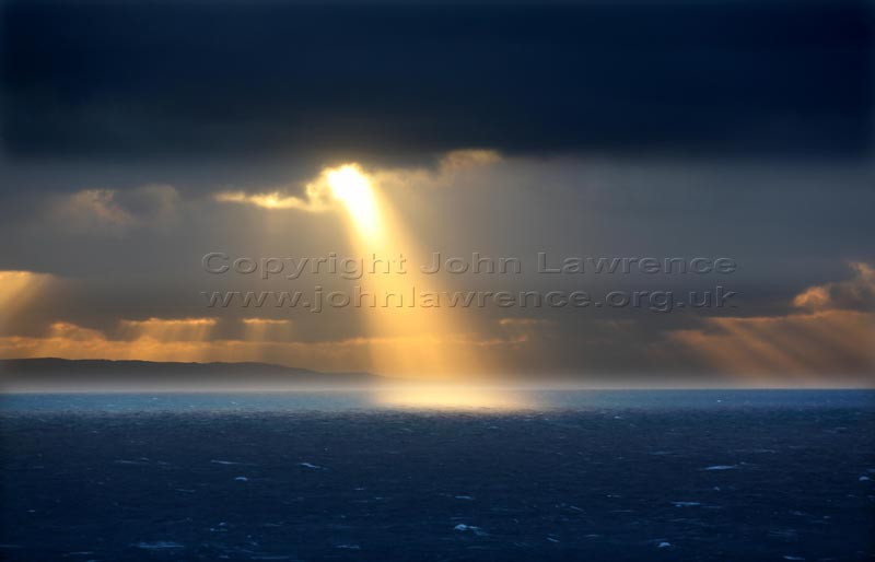 sun beam over the open sea in cornwall