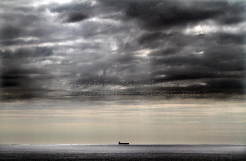 storm clouds over the sea with a silhouette of a ship in the distance