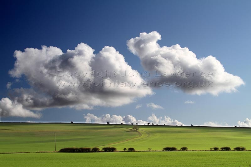 green countryside hills with a blue sky and clouds